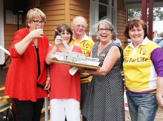 • Announced as Citizen of the Year during the Corner Inlet Australia Day festivities, Sandy Bucello enjoys a traditional Aussie lamington, cut by Kerry Cripps and served by Deputy Mayor Moyha Davies. Representing Event of the Year  are South Gippsland Relay for Life are Chair Meg Edwards and (at rear) Richard Jones of the relay team the 'Ramblin' Rotarians.' See page XXX for full story.
